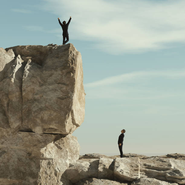 Man looks up to another man celebrating on the top of mountain cliff. This is a 3d render stock photo