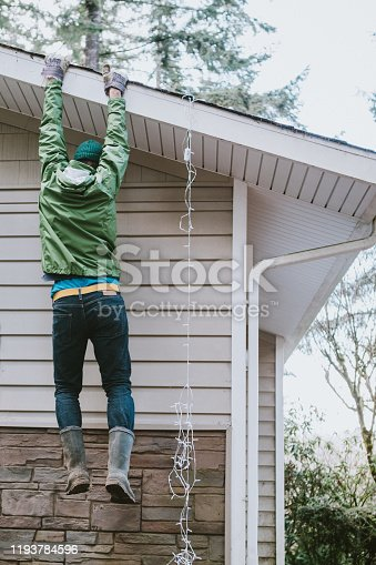 An accident occurs while hanging holiday lights on the home; a man has his ladder slip out from under him and hangs dangerously from the roof edge.