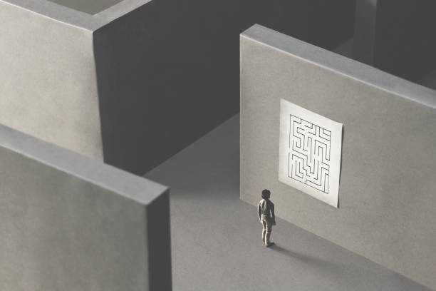 man lost in a complex maze, observing the map to find the way out;  surreal concept stock photo