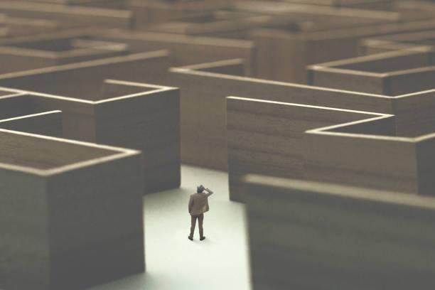 man lost in a complex maze, surreal concept stock photo