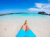 Caucasian man lying and enjoying on a sandy tropical beach. POV.