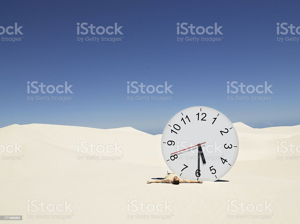 A man lying by a clock in the desert royalty-free stock photo
