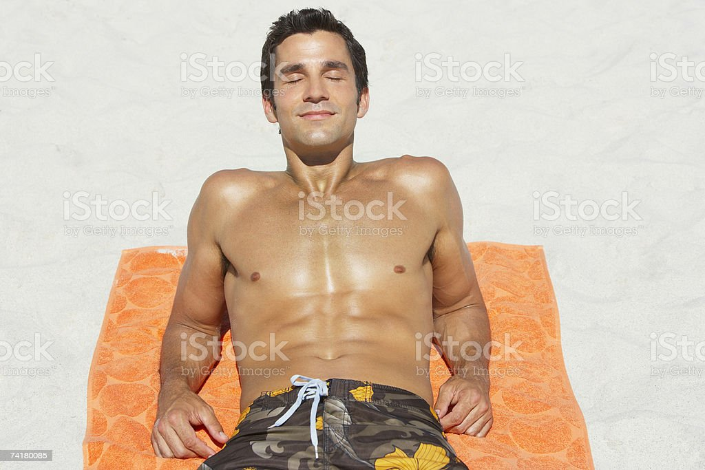 Man lying down on beach towel in sand stock photo