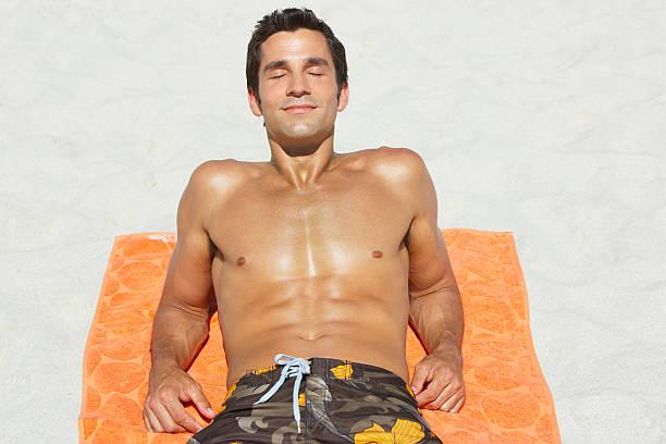 Man lying down on beach towel in sand stock photo