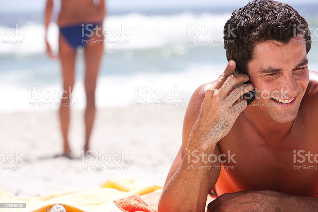 Man lying down on beach towel in sand with cell phone  stock photo