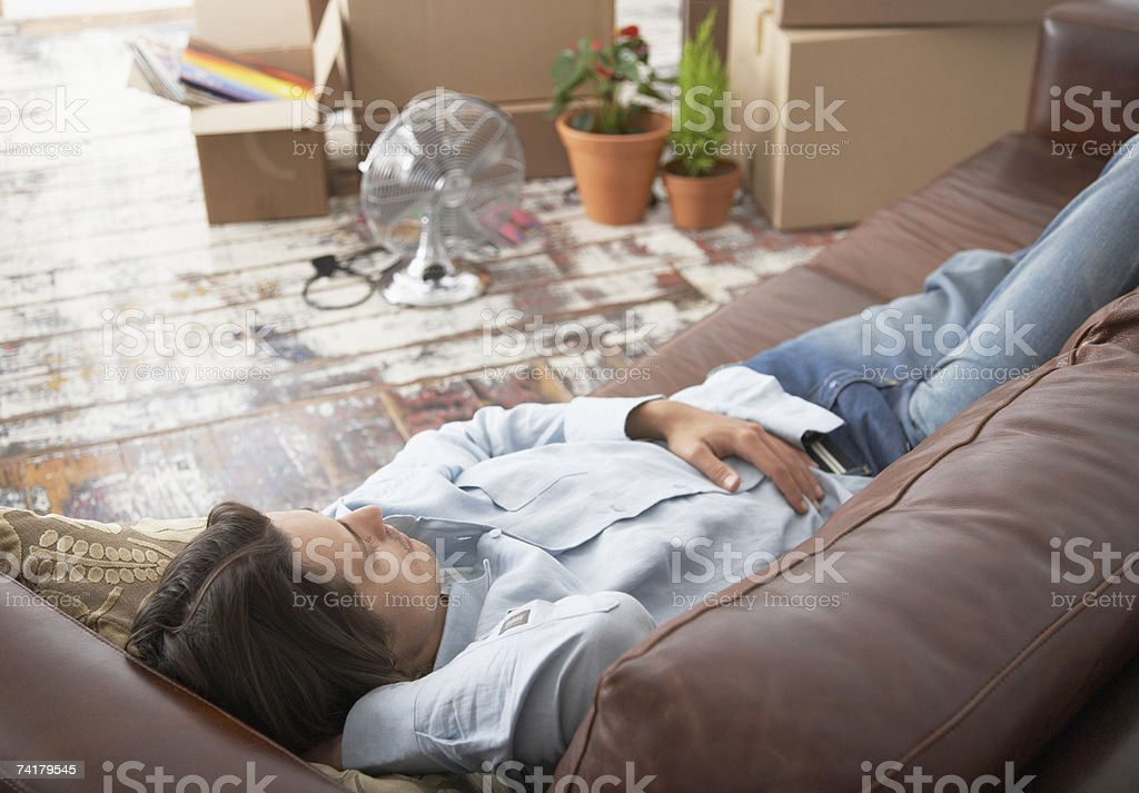 Man lying down on sofa in home with cardboard boxes royalty-free stock photo