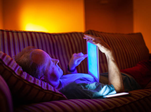 Man lying down on the couch in the evening, with blue light from tablet stock photo
