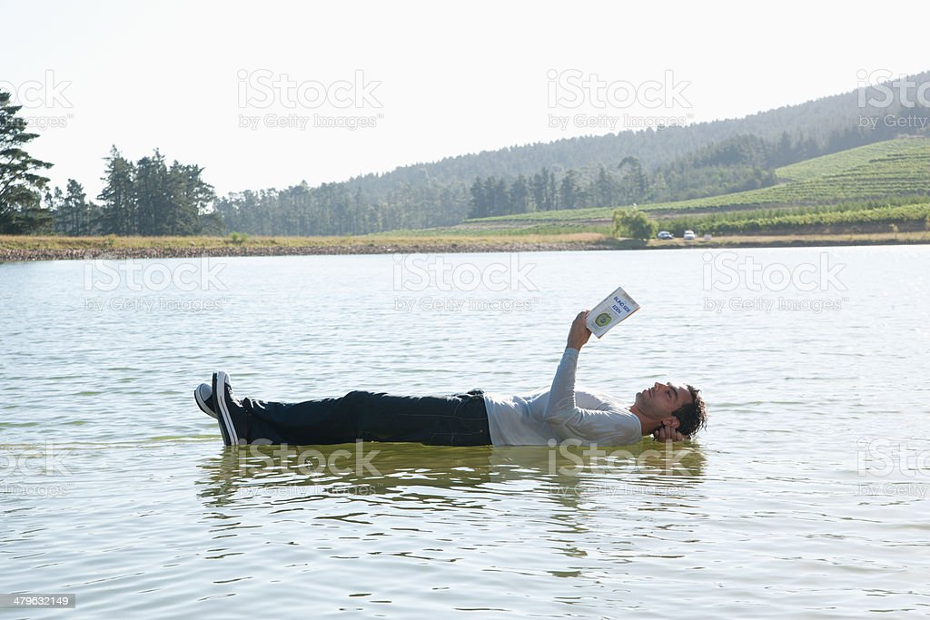 Man lying down on water reading book stock photo