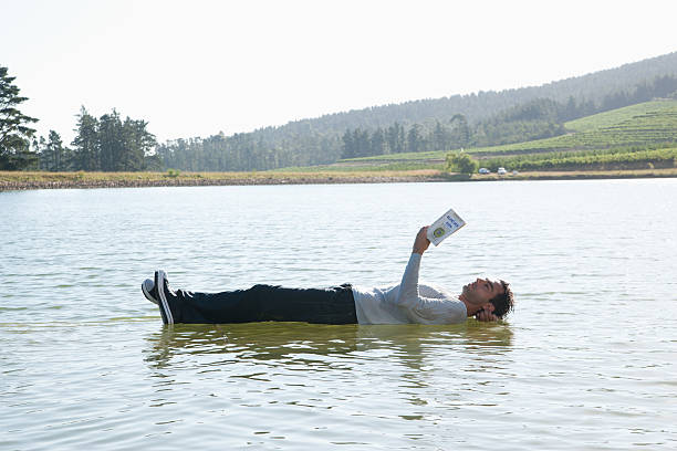 man lying down on water reading book - illusion stock photos and pictures
