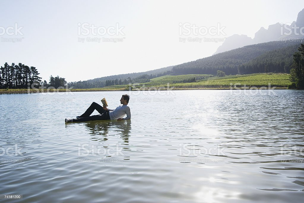 Man lying down on water reading book royalty-free stock photo