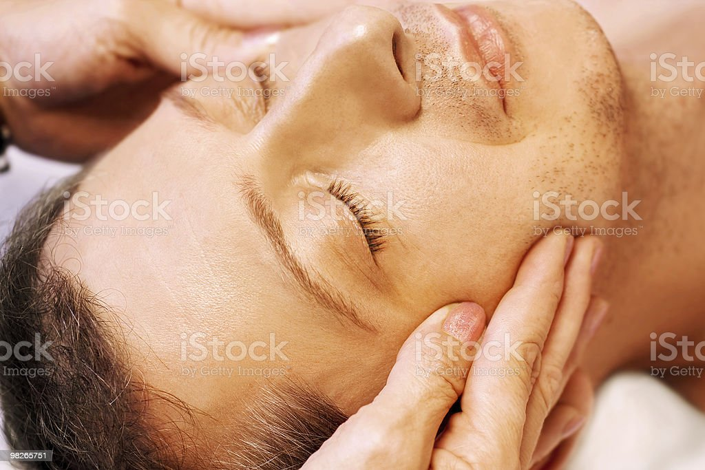 Man lying, gets facial massage royalty-free stock photo