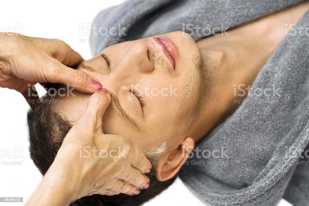 man lying, gets massage, reiki,acupressure on his face royalty-free stock photo