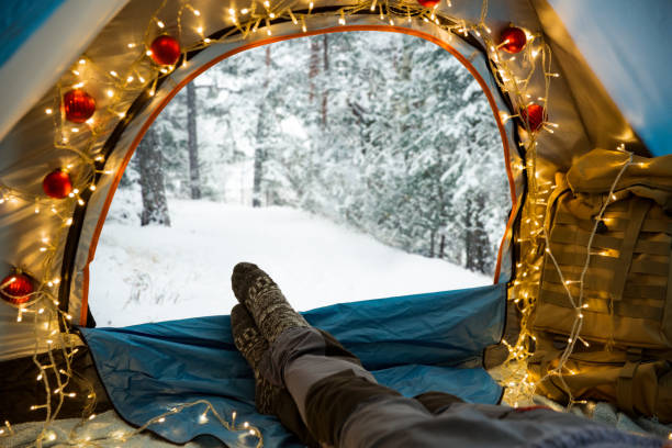 A man lying in a tent decorated with Christmas lights stock photo
