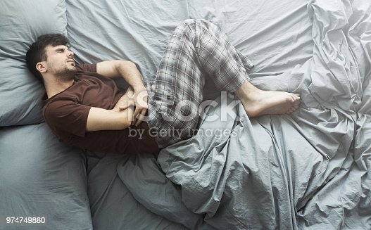 Young man suffering from stomach ache, lying in bed at home, top view. Health problems concept