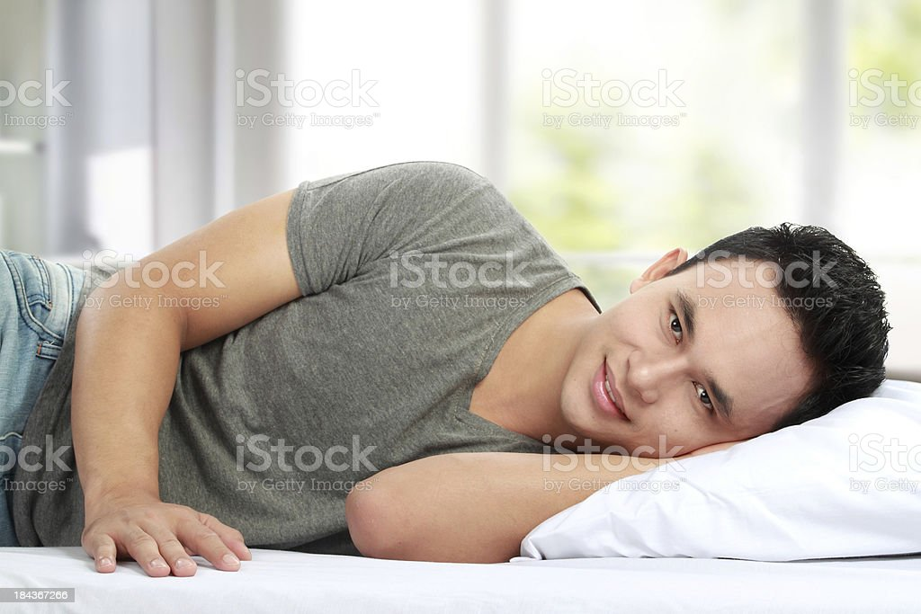 Man lying in bed smiling royalty-free stock photo
