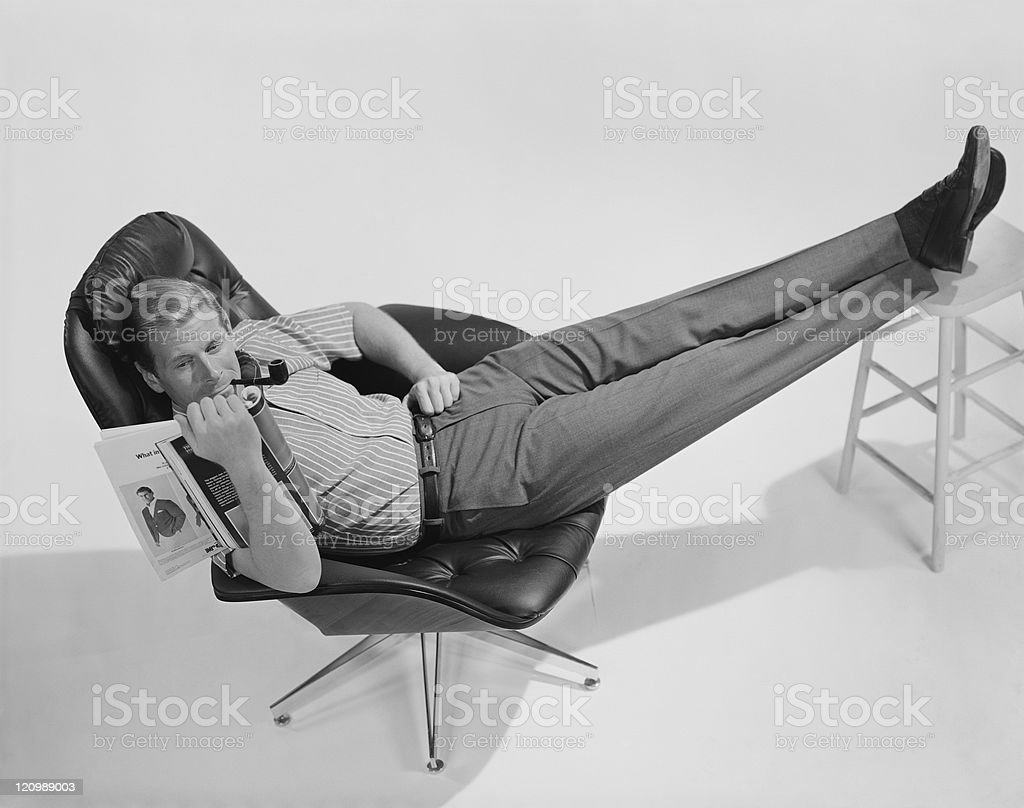 Man lying in chair and reading magazine stock photo