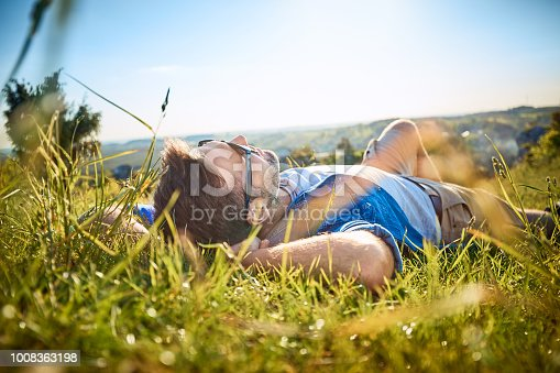 Man lying in grass on hiking trip in the mountains