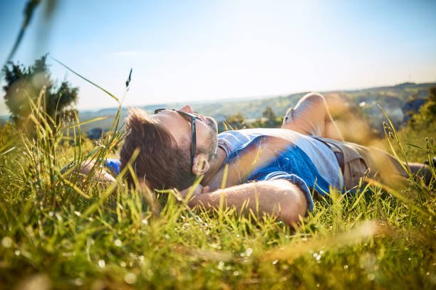 Man lying in grass on hiking trip in the mountains stock photo