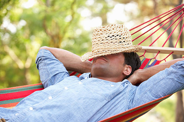 man lying in hammock - hangmat stockfoto's en -beelden