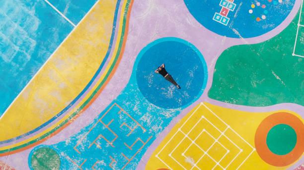mann liegen inmitten einer bunten spielplatz und die erinnerung an seine kindheit - spielplatz design stock-fotos und bilder