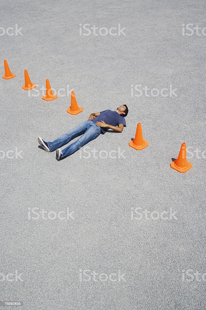 Man lying in-between a row of safety cones royalty-free stock photo