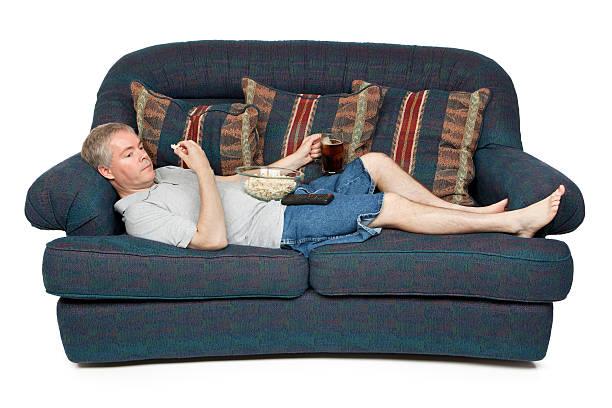 uomo sdraiato su un divano - divano procrastinazione foto e immagini stock