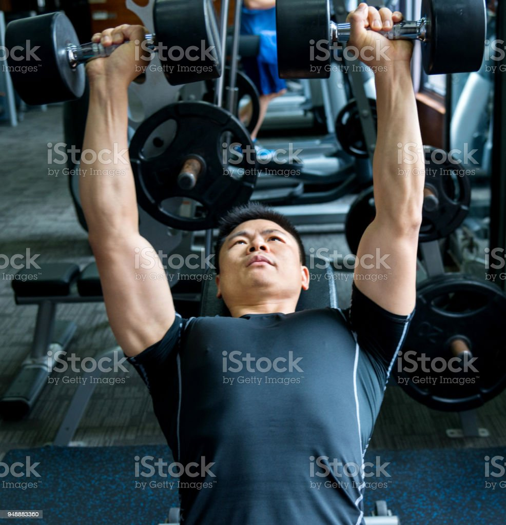 Man lying on exercise bench and lifting dumbbells stock photo
