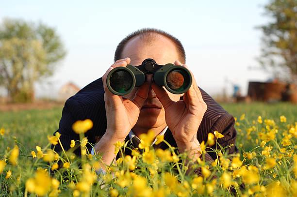 Man lying on flowers and looking through binoculars stock photo
