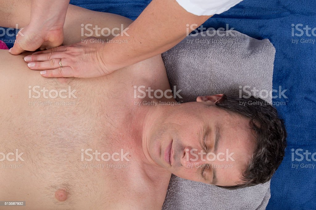 Man lying on his back  having a shoulder massage stock photo