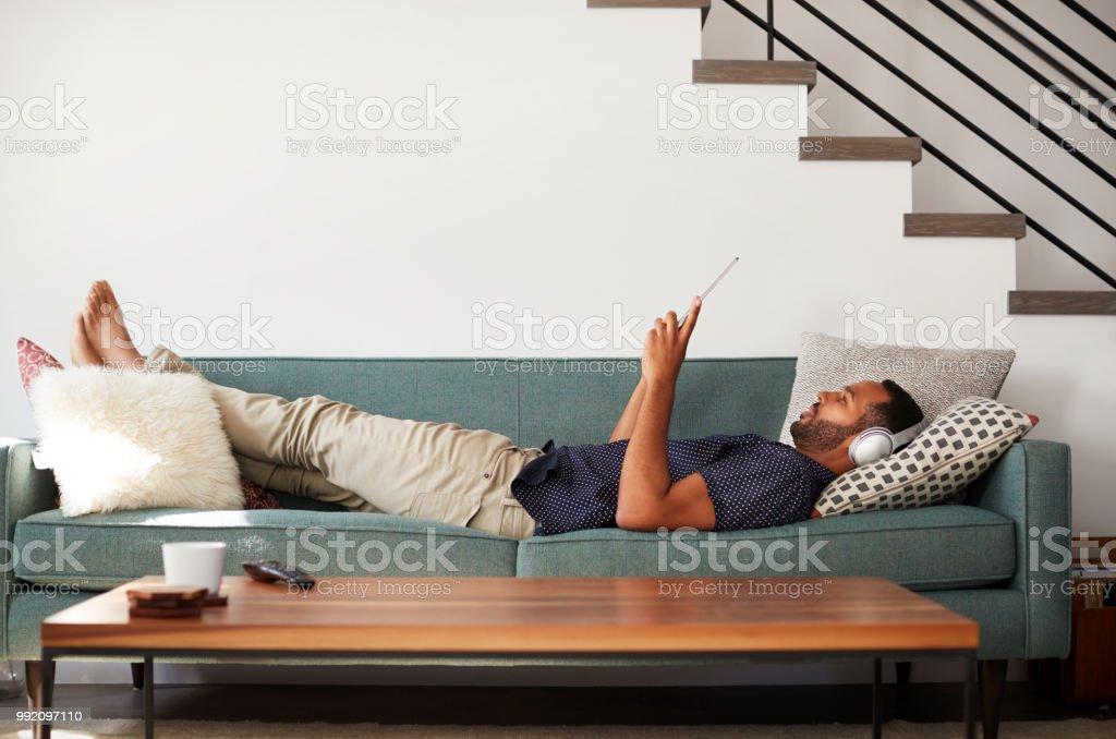 Hombre acostado en el sofá en casa con los auriculares puestos y viendo la película en tableta Digital - Foto de stock de 20 a 29 años libre de derechos
