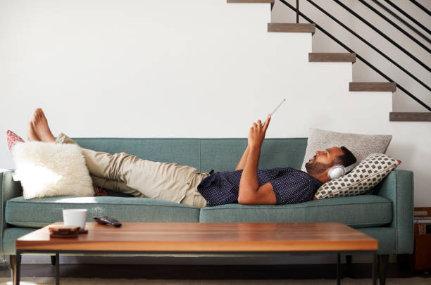 man lying on sofa at home wearing headphones and watching movie on digital tablet - guy sofa foto e immagini stock