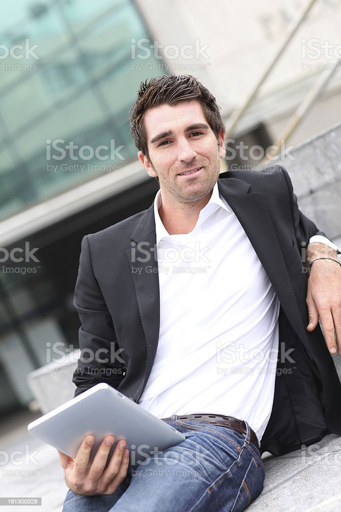 Man lying on stairs outdoors with tablet in hands royalty-free stock photo