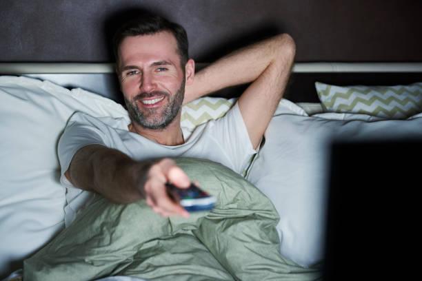 Mann auf dem Bett liegend und vor dem Fernseher in der Nacht – Foto