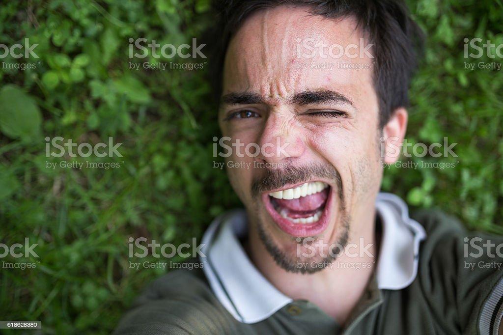Man lying on the clover field,making selfie stock photo