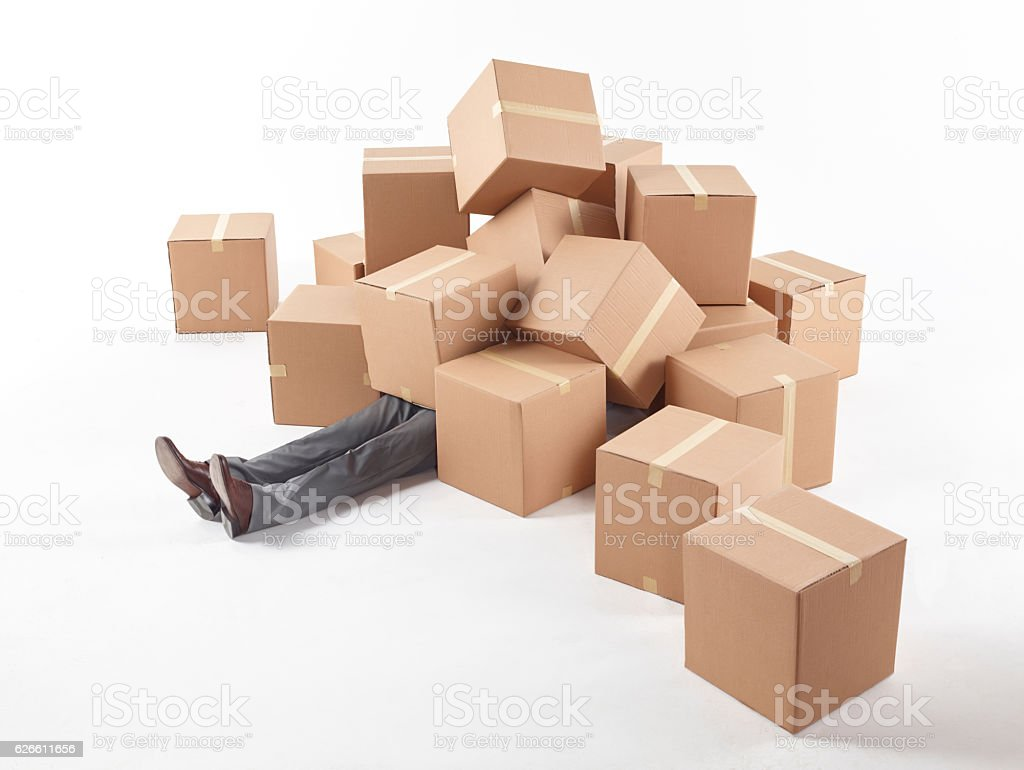 Man lying on the floor covered with boxes stock photo