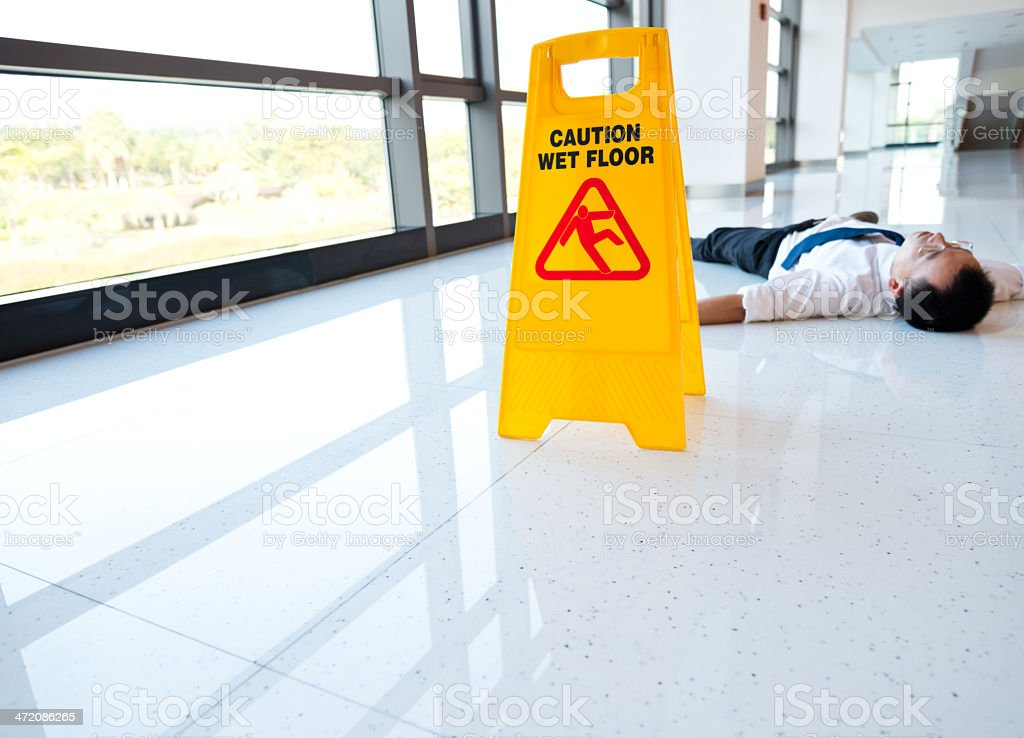 Man slips falling on wet floor next to the wet floor caution sign.