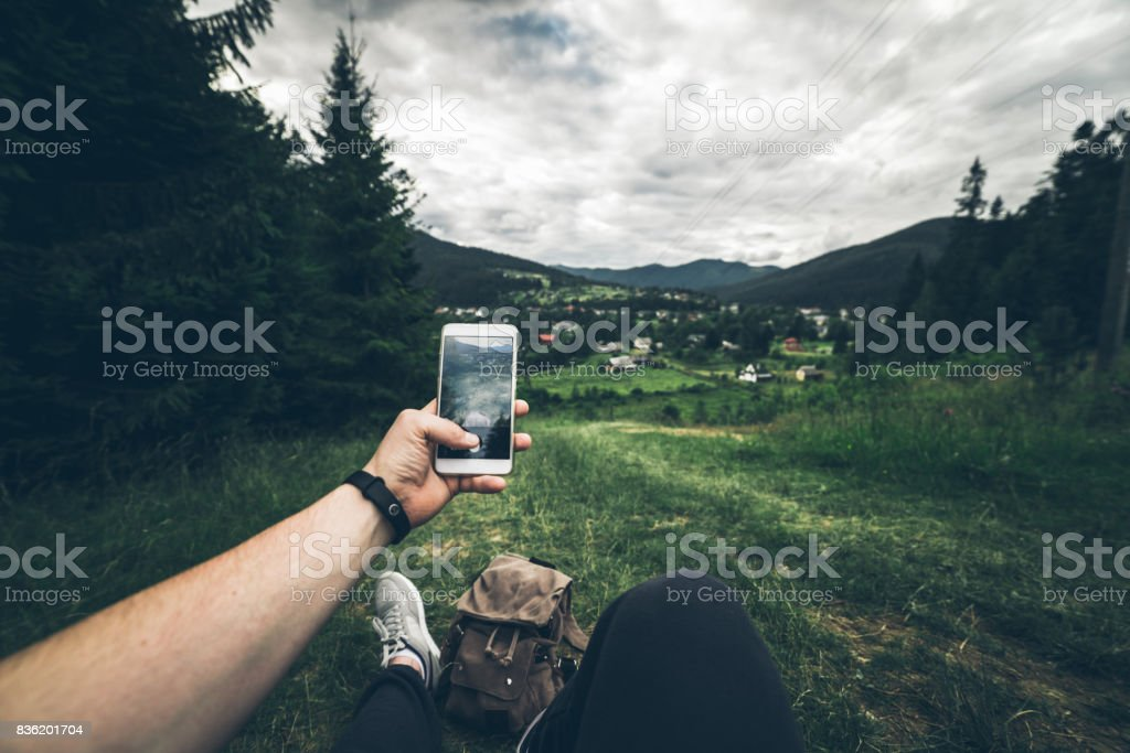 man lying on the ground and taking picture of mountains stock photo