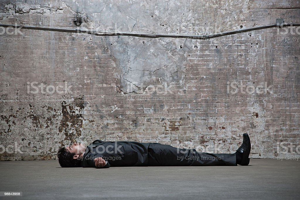 Man lying on warehouse floor royalty-free stock photo