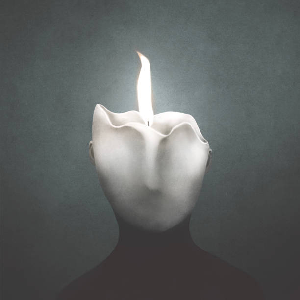 Man made of wax melting under the heat of a flame, surreal concept stock photo