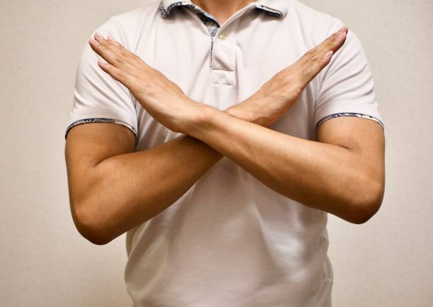 man made X sign shape mean to say no man in white T-shirt made X sign shape mean to say no forbidden stock pictures, royalty-free photos & images