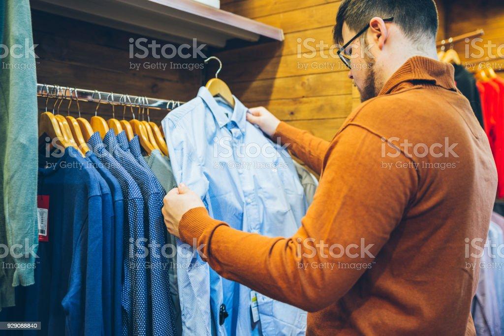 man make shopping in store. choose shirts in shop stock photo