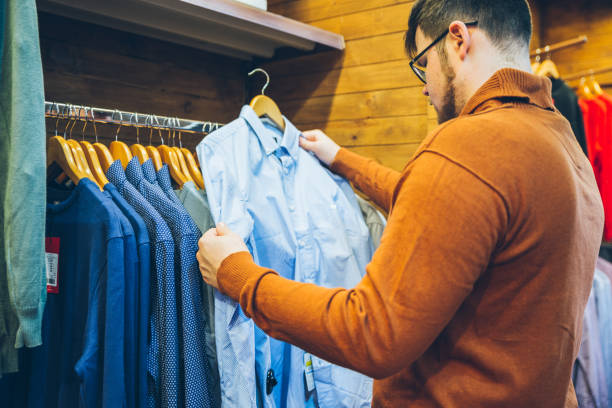 man make shopping in store. choose shirts in shop stock photo