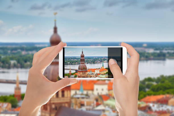 A man makes a photo of Riga A man is making a photo of view of the city of Riga from above including the tower of the Dome Cathedral on a mobile phone taken on mobile device stock pictures, royalty-free photos & images