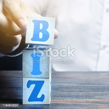 A man makes a word BIZ out of blocks. Creation of sites on the top-level domain for business. Promotion of the company and products on the network.