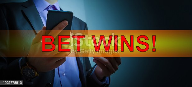 843298172 istock photo man makes bets on a smartphone 1205778813