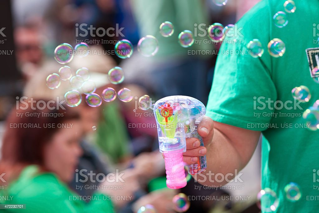 Man Makes Bubbles With Bubble Pistol At Parade stock photo