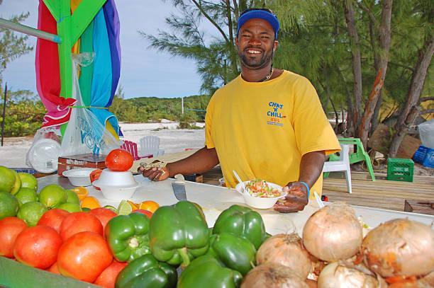 mann macht muschelsalat auf den bahamas beach - kochinsel stock-fotos und bilder