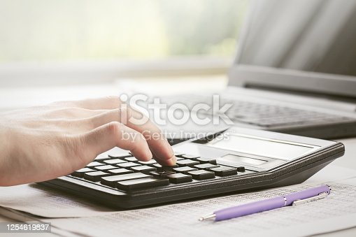 490632340 istock photo man makes financial report, considers it on calculator and writes it in documents. 1254619837