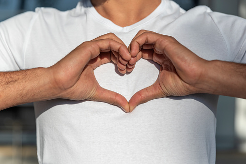 man making a heart symbol with hands