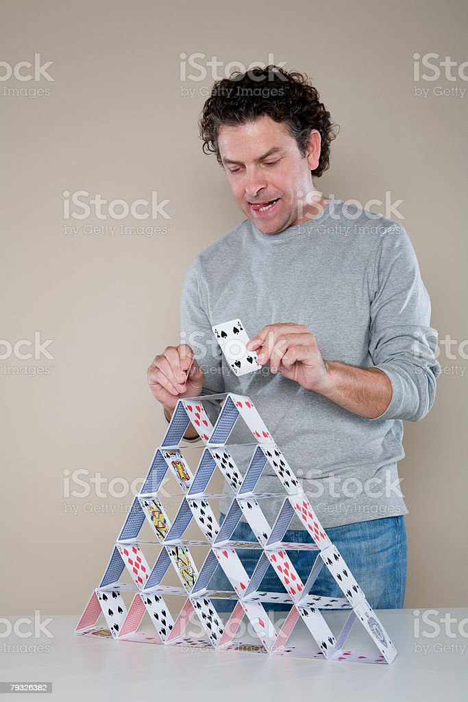 Man making a house of cards stock photo